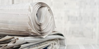rolled newspaper on stack of newspapers against blurry background